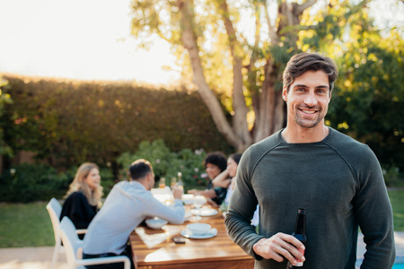 Handsome young man standing outdoors with friends sitting in background having food. Man with beer at outdoor party.