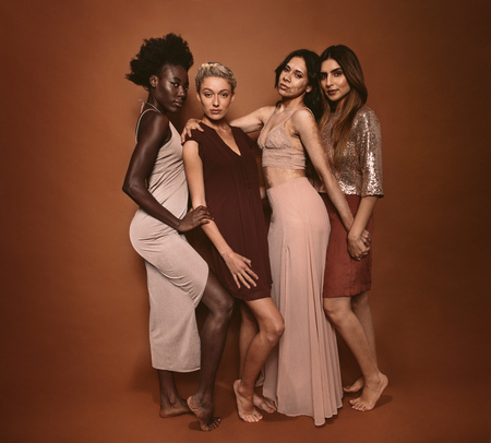 Group of four beautiful young women standing against grey background. Stylish diverse models posing together in studio.