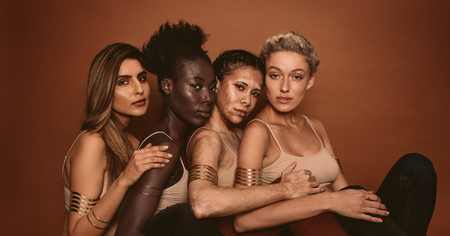 Portrait of female models with different skins. Group of young women sitting together and looking at camera on brown background.
