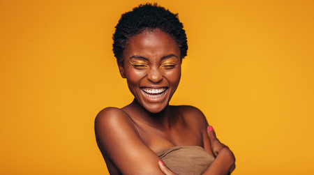 Young african woman laughing against yellow background. Cheerful female model with vivid makeup. Stock fotó - 91247359