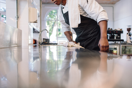 Cropped shot of waiter wiping the counter top in the kitchen with cloth. Man cleaning and maintaining commercial kitchen hygiene.
