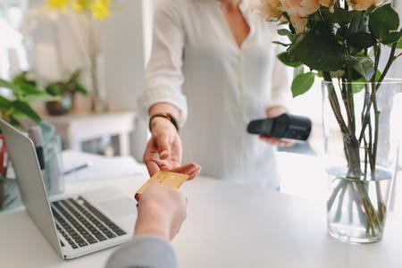 Jonge vrouw die bij bloemwinkel werkt die creditcard van klant neemt. Bloemist die betaalpas accepteert voor betaling van klant.