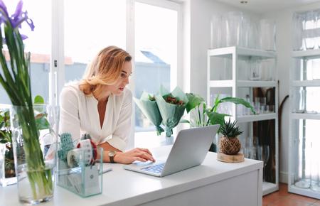 fleuriste femme utilisant un ordinateur portable au comptoir dans un magasin de fleurs petit bureau utilise un travail d & # 39 ; ordinateur portable sur son ordinateur dans son magasin.