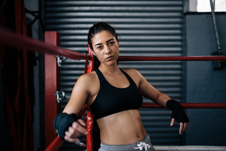 Female boxer sitting in one corner of a boxing ring with her hands resting on the ropes. Boxer training at a boxing studio. Stock Photo