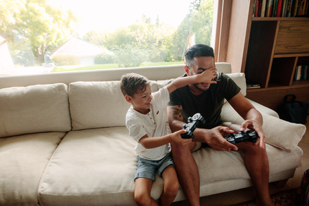 Cheerful family of father and son having fun playing video games at home. Little boy covering eyes of his father while playing video game in living room. Reklamní fotografie