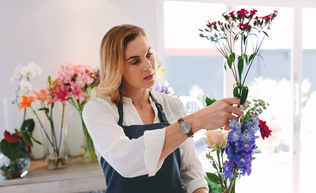Female working at flower shop arranging flowers. Woman florist making bouquet with various flowers.