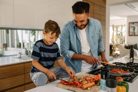 Vegetais do corte do rapaz pequeno quando seu pai que cozinha o alimento na cozinha. Pai e filho que preparam a cozinha do alimento em casa. Foto de archivo