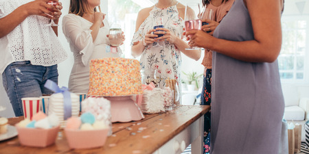 Cropped shot of cake and sweet food on table with women standing around holding drinks at baby shower party. Female friends enjoying baby shower party.