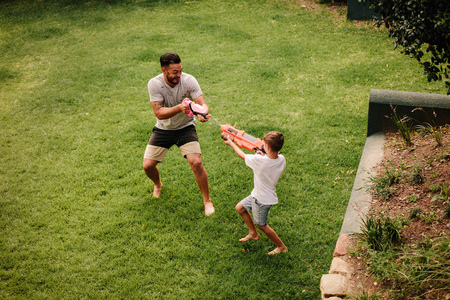 Boy playing water guns with father in backyard lawn. Father and son playing water gun fight outdoors. Reklamní fotografie - 91510424
