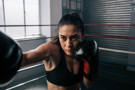 Boxer practicing her punches at a boxing studio. Close up of a female boxer punching with her boxing glove on inside a boxing ring.