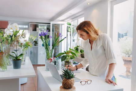 Young female florist making notes at flower shop counter with laptop. Woman working in plant nursery.