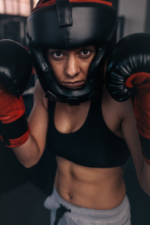 Close up portrait of a female boxer in her boxing gear. Woman boxer at a boxing studio wearing head guard and boxing gloves. Banco de Imagens