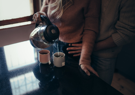 Woman standing by kitchen making coffee and her boyfriend embracing from behind. Cropped shot of romantic man and woman in kitchen making coffee. 写真素材