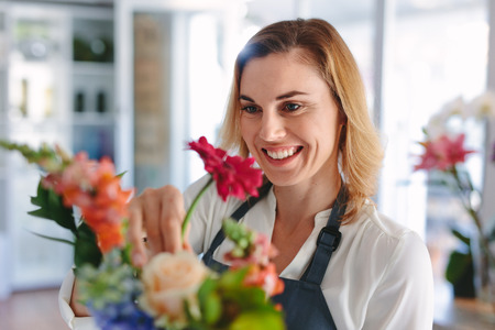 Smiling female florist preparing a bouquet. Woman making a bouquet of fresh flowers at retail shop.