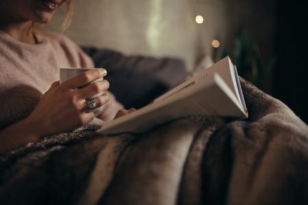 本とコーヒーで女性の手のトリミングショット。夜ベッドの上で女性の読書本。 写真素材