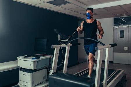 Coureur masculin avec masque en cours d'exécution sur une machine de tapis roulant testant ses performances. Athlète examinant son aptitude au laboratoire de biomécanique.