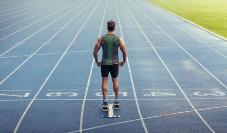 Hintere Ansicht eines Athleten bereit, auf eine Allwetterlaufbahn zu sprinten. Läufer, der einen Startblock verwendet, um seinen Lauf auf Rennstrecke zu beginnen. Standard-Bild - 91758365