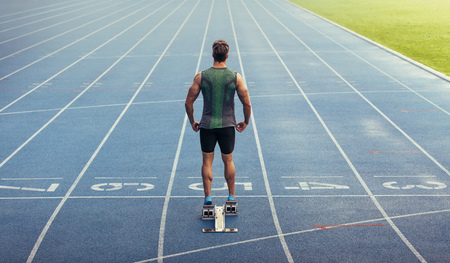 Rear view of an athlete ready to sprint on an all-weather running track. Runner using a starting block to start his run on race track.