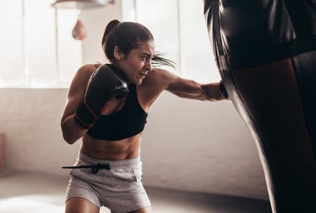 Vrouwelijke bokser die een reusachtige bokszak raakt bij een boksstudio. Vrouwenbokser die hard opleiden.