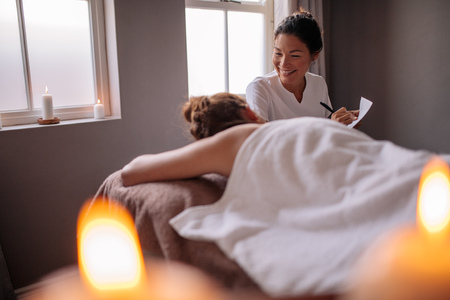 Kosmetiker, der weiblichen Kunden vor Badekur überprüft und Anmerkungen für die Therapie macht. Weiblicher Massagetherapeut, der mit Frau in der Wellnessmitte spricht und Anmerkungen macht.