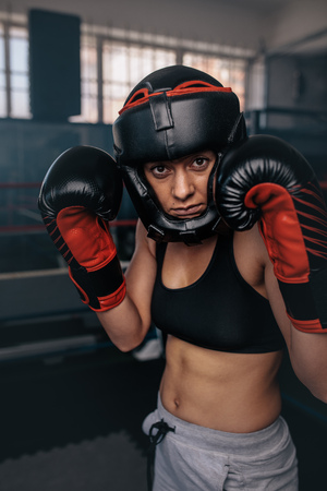 Close up of a female boxer in her boxing gear. Woman boxer at a boxing studio wearing head guard and boxing gloves. Banco de Imagens