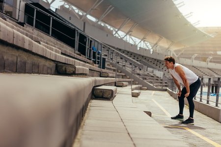 Athlete doing exercise in the stands of a track and field stadium. Runner standing with hands on knees in the stands.