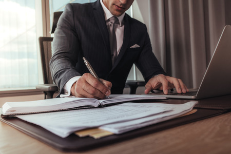 Cropped shot of businessman hands writing in a diary. Man working at his office desk with laptop.