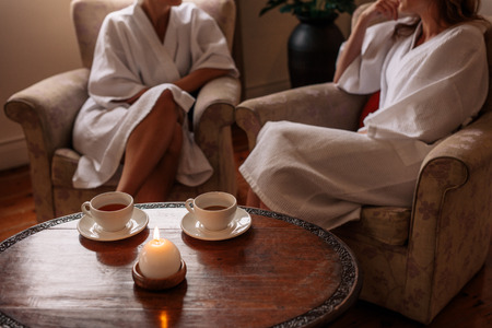 Spa waiting area with women sitting in background. Focus on table with candle and herbal tea cups. Stock fotó