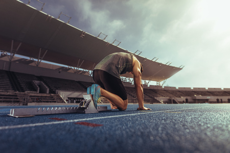 Rear view of an athlete on his mark ready to sprint on running track. Runner using a starting block to start his run on race track in a stadium.