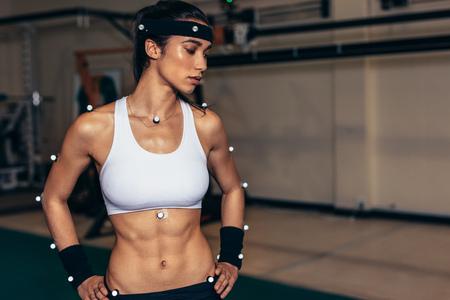 Laboratorio de biomecánica. Atleta femenina con sensores de captura de movimiento en su cuerpo para registrar el movimiento y el rendimiento. Foto de archivo