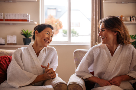 Two smiling women in bathrobe sitting in reception area and talking before spa treatment. Two female friends relaxing in beauty spa waiting room and smiling.