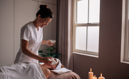 Young woman having spa procedure on her face. Woman lying on spa table and cosmetologist applying cosmetic mask on the her face in sap salon.