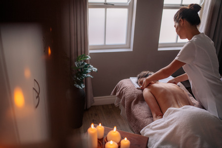 Massage therapist massaging back and shoulders of a woman lying on table. Woman receiving body massage at spa center Foto de archivo