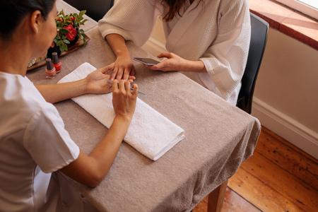 Frau im Salon , der eine Maniküre durch Kosmetiker empfängt . Kosmetikerin , die weibliche Nägel am Badekurortsalon empfängt