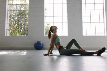 Tired woman taking rest after workout. Tired and exhausted female athlete sitting on floor at gym.