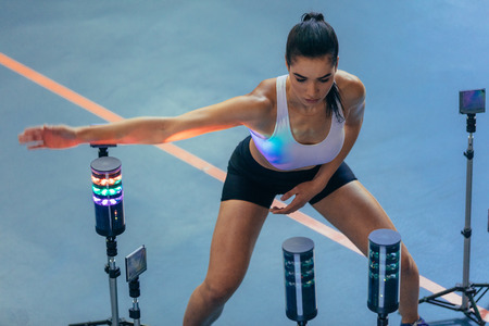 Sportswoman exercising with lights around, reaction training session at gym. Female athlete using a visual stimulus system to improve reaction time at sports lab.