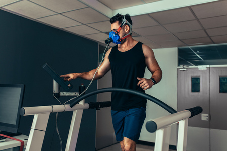 Performance testing. Runner with mask on treadmill in sports science laboratory. Athlete walking on a treadmill and measuring his performance and oxygen consumption.