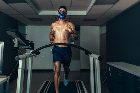 Fit young man running on treadmill with a mask in sports lab. Athlete examining his performance in sports science lab. Stock Photo