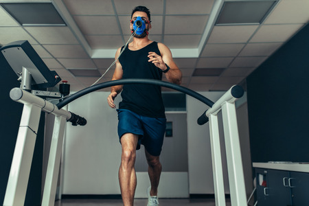 Athlete examining his fitness in sports lab. Runner with mask running on treadmill machine and testing performance.