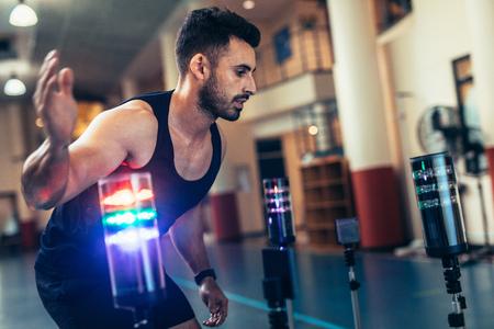 Atleta utilizando un sistema de estímulo visual para mejorar el tiempo de reacción. Deportista en el laboratorio de ciencias deportivas haciendo ejercicio con luces alrededor. Sesión de entrenamiento de reacción en el gimnasio. Foto de archivo - 92699670