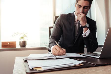 Young businessman sitting at office with laptop and taking notes. Male entrepreneur working at his desk.