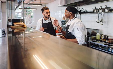 商業用キッチンで働く制服を着た2人の男性料理人。プロのシェフがレストランのキッチンで一緒に調理した新しい料理の味を議論します。