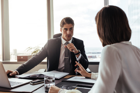 Businessman listening to the suggestions from female colleague. Two corporate professionals having a meeting in office.