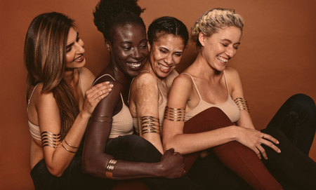 Smiling female models with different skins. Group of multi ethnic young women looking happy together on brown background.