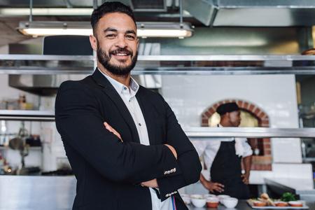 Portrait de jeune homme debout dans son restaurant avec du personnel de cuisine. Fier propriétaire du restaurant, les bras croisés et regardant la caméra.