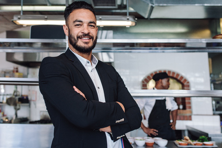 Portrait of young businessman standing in his restaurant with staff in kitchen. Proud restaurant owner standing with his arms crossed and looking at camera.