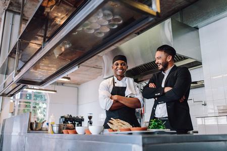 Glimlachende restauranteigenaar en chef-kok die zich in keuken bevinden. Zakenman met professionele zich verenigen en kok die lachen.