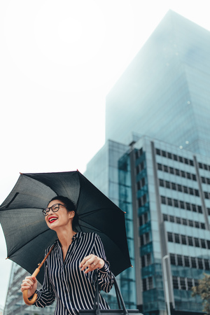 Urban woman smiling on the city street with umbrella. Businesswoman outdoors in the city holding umbrella and smiling.