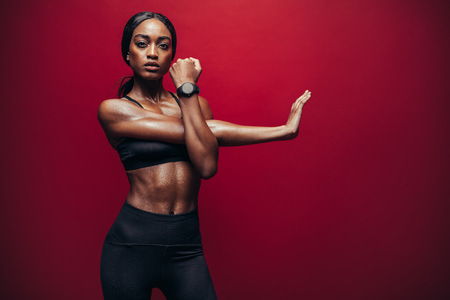 Fit woman doing exercise against red background. African female doing arm stretching exercise to keep a good flexibility of her biceps. Banco de Imagens