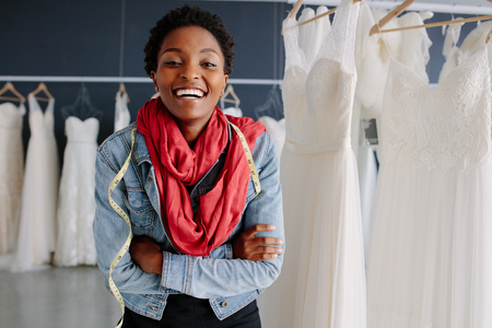 Portrait of african female bridal store owner standing with her arms crossed and smiling. Woman tailor standing in wedding fashion shop.